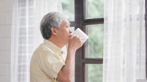 Old asian man drinking coffee looking out of window